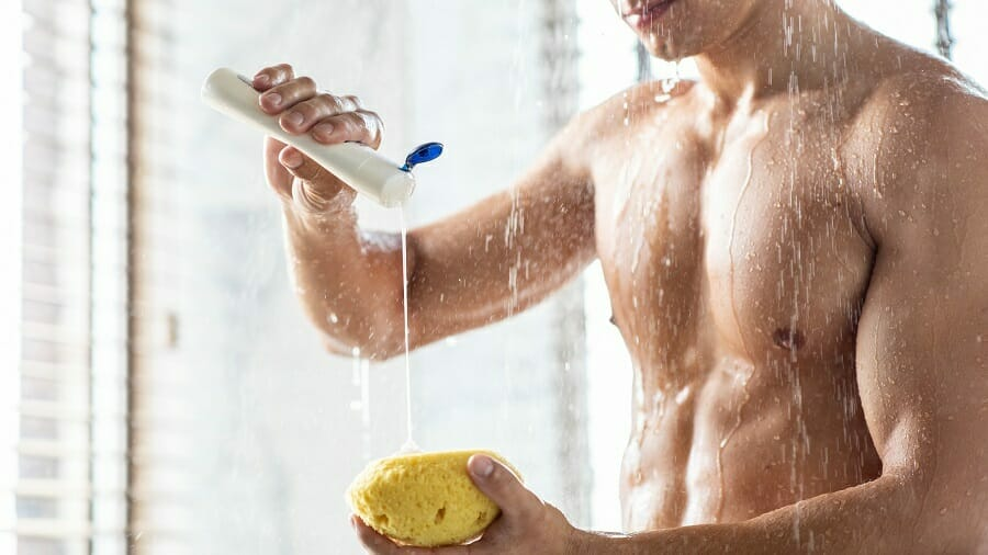 Man taking a shower pouring shampoo onto yellow sponge