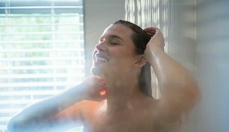 Woman taking a shower in bathroom
